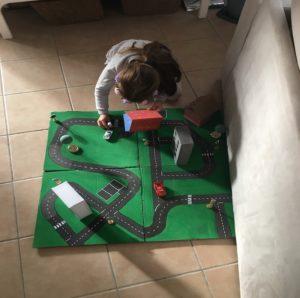 Emma peut maintenant jouer avec son parking fait-maison à partir de matériaux récupérés.