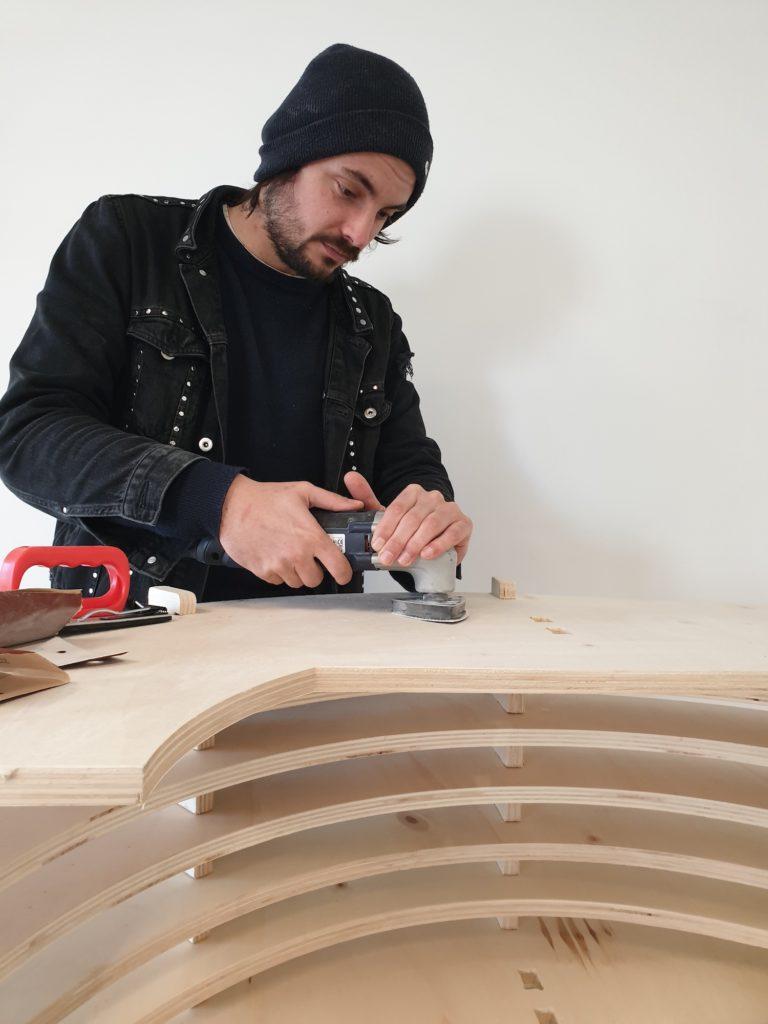 Antoine, créateur du Rambot du Cactus qui monte le mobilier de son futur espace.